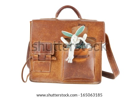 brown shoulder bag with cute toy rabbit in pocket, isolated - stock photo