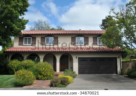 Brown single family house with grass and shrubs in front