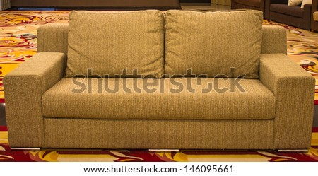 Brown sofa with cushions and beautiful carpet.