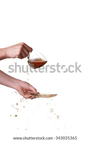 Brown splashes out drink from glass on a white background.