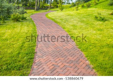 Brown stone pathway in the park background. Brown concrete pathway with green grass lawn in the park backdrop