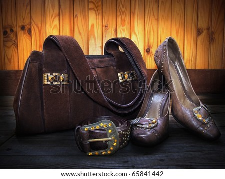 Brown suede bag, leather shoes and belt decorated by yellow and orange artificial gems - stock photo