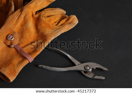 Brown suede leather work gloves and chrome plated slip joint pliers on a black background - stock photo