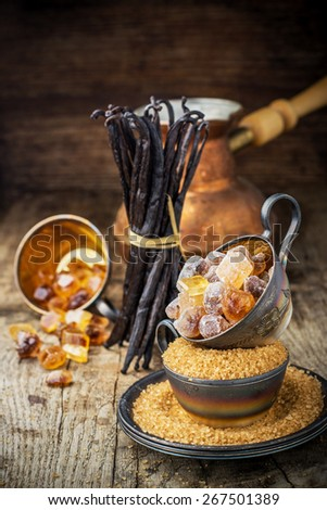 Brown sugar  crumbly, caramel, crystals, vanilla pods, star anise, cinnamon, spices with vintage metal cup on a wooden background. selective Focus - stock photo