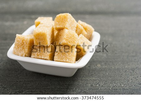 brown sugar cubes on white square dish, dark wood table