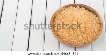 Brown sugar in a bowl over wooden background