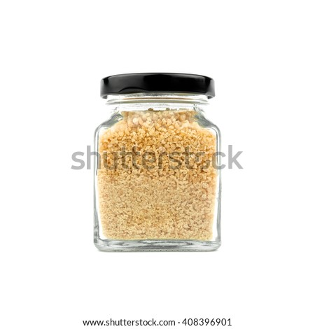 Brown sugar in a glass bottle isolated on white background. Granulated sugar. Black lid. Modern and stylish. Close up. - stock photo