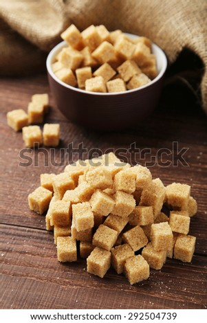 Brown sugar in bowl on brown wooden background