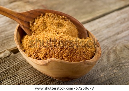brown sugar over spoon on wood background - stock photo