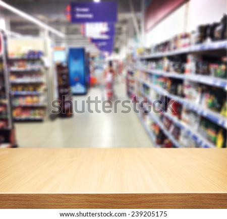 Brown table and on background blured supermarket. Empty space for you design - stock photo