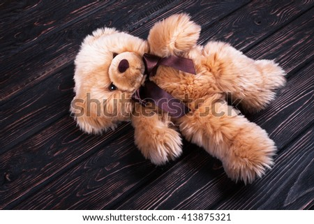 Brown teddy bear on wooden boards. Teddy bear with a bow - stock photo