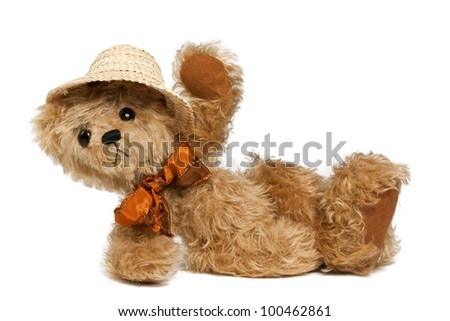 Brown Teddy bear with Bow and Summer Hat lying Down,  isolated on white