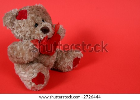Brown Teddy Bear with hearts on red background