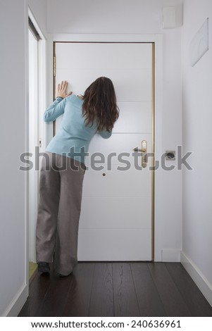 brown trousers green jersey woman back looking to peephole interior house hall white door wooden floor