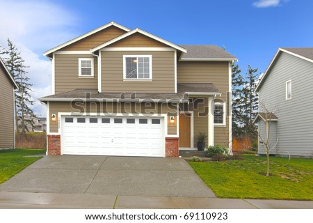 Brown  two level house with large garage door - stock photo