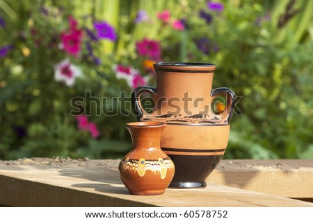 Brown vases with a flower background - stock photo