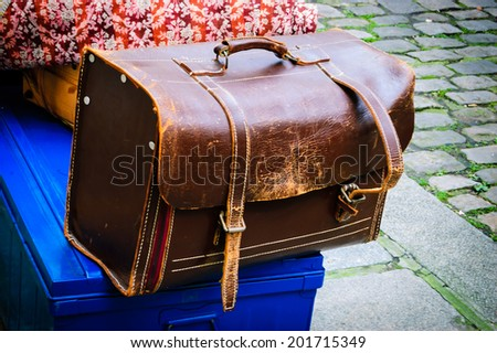 Brown vintage leather briefcase with two straps and brass buckles against pavement background. Old Times concept. Shadowed angles. - stock photo