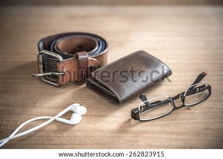 brown wallet,belt, spectacles,earphones  vintage style, selective focus on wallet - stock photo