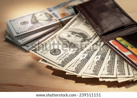 Brown Wallet with credit cards and dollar banknotes over wooden background. Shallow depth of field. - stock photo