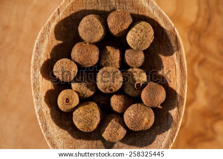 Brown whole allspice dry fruits portion on wooden spoon macro, Pimenta dioica raw spice unripe berries heap in day light, horizontal orientation, nobody.  - stock photo