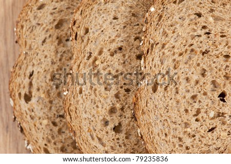 Brown whole wheat bread slices on wooden plate