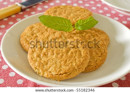 Brown wholemeal biscuits on a white plate - stock photo