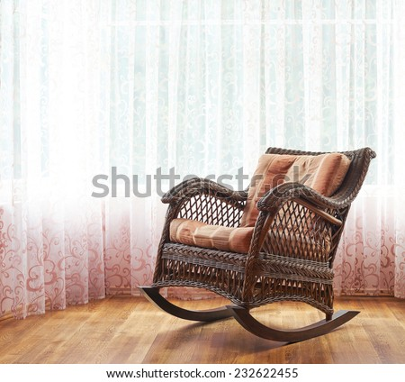 brown wicker rocking chair against the curtains indoor composition