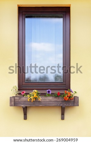 Brown window with flowers in hanging flower pot - stock photo