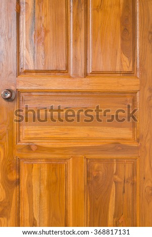brown wood door with door knob and keyhole in residential house - stock photo