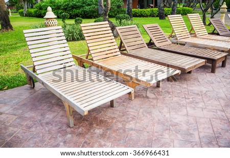 Brown wooden beach chairs and side table on wood floor near swimming pool