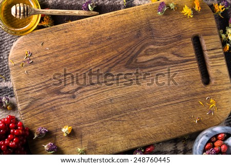 Brown wooden board as space for text surrounded by herbs, berries in the marble pot, top view - stock photo