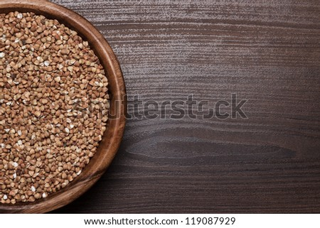 brown wooden bowl full of buckwheat background - stock photo