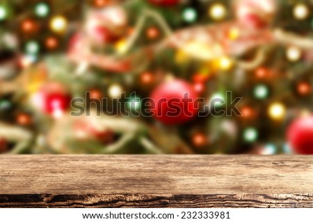 brown wooden desk space and xmas time of tree and lights  - stock photo