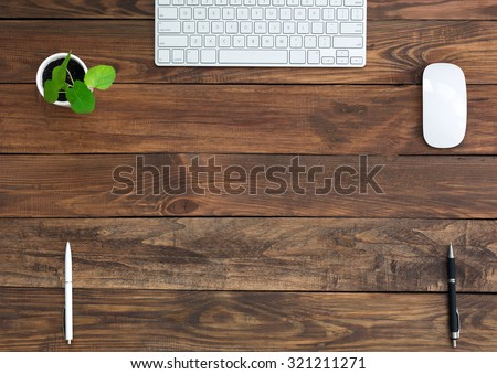 Brown Wooden Desk with Stationery and Electronics Natural Wood Background Small Green Plant Computer Mouse and Keyboard Black and White Pens Top View - stock photo