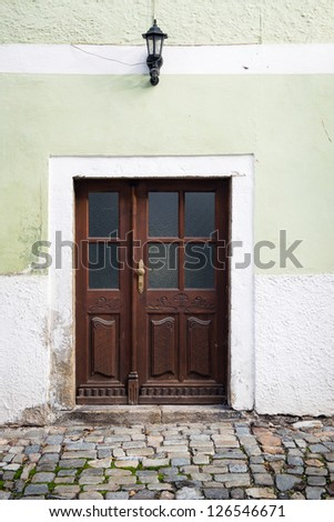 brown wooden door and lamp in house with green facade