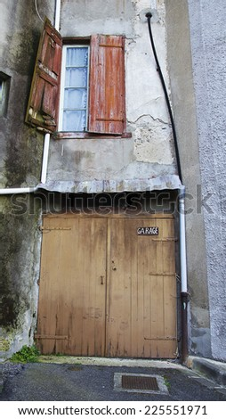 Brown wooden garage door closed. Old thin stone private with a red window building.