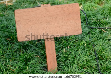 Brown wooden signboard against grass background