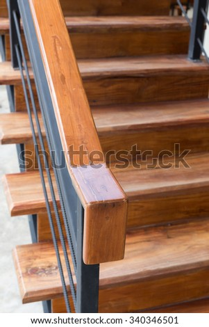 brown wooden staircase with iron banister in modern house - stock photo
