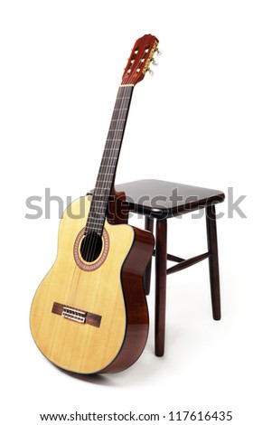 brown wooden stool and a six string guitar - stock photo