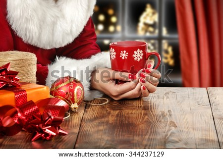 brown wooden table and red mug in hands and ball  - stock photo