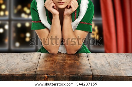 brown wooden table and woman elf in green dress  - stock photo