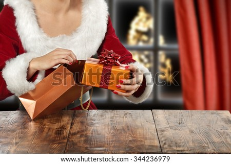 brown wooden table and xmas tree window and box  - stock photo