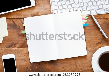 Brown wooden table, top view. On the table are, stationery items, notebook, gadgets,  stickers, keyboard,coffee, mouse, white paper,notebook, for convenient operation. - stock photo