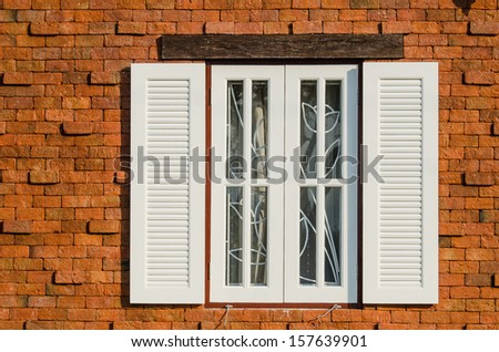 Brown wooden window on brick wall in sunny day