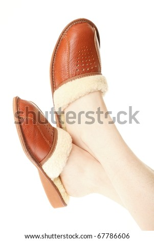 brown wool comfortable slippers on the foot - house slipper isolated on white background - stock photo