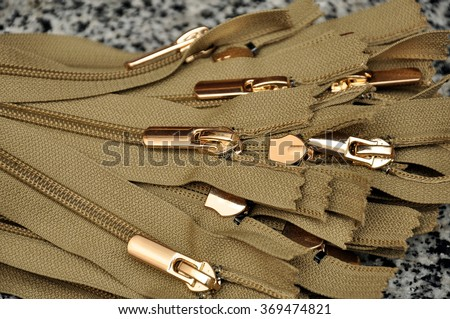Brown zipper close up. Many black zippers background. - stock photo