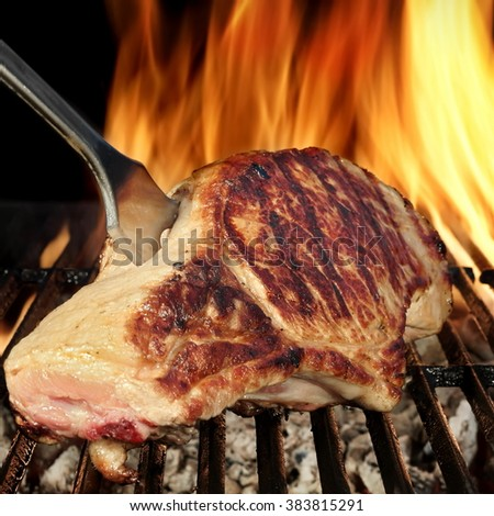 Browned Pork Loin Steak On The Hot Barbecue Charcoal Grill With Fork, Bright Flames Of Fire On The Black Background, Close Up, Front  View, Cookout Food For Outdoor Party Or Picnic
