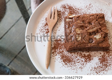 Brownie almonds./Brownie./Brownie almond put on white plate. Sprinkle with cocoa powder served with whipped cream. - stock photo