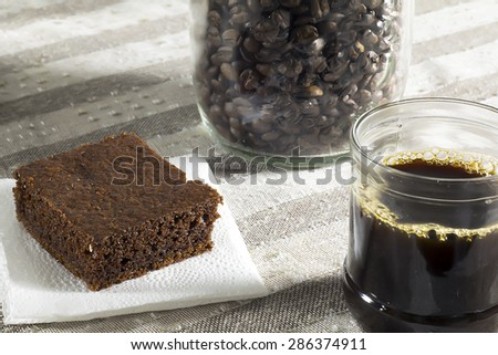 brownie, black coffee, mason jar filled with coffee beans. - stock photo