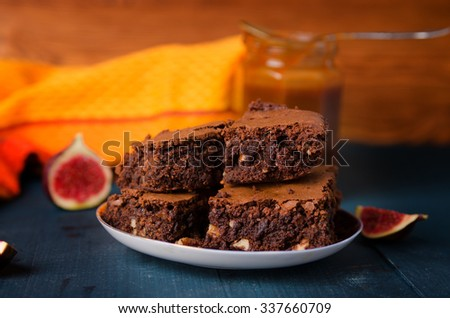 Brownie with walnuts, figs on a dark blue background with a yellow cloth - stock photo
